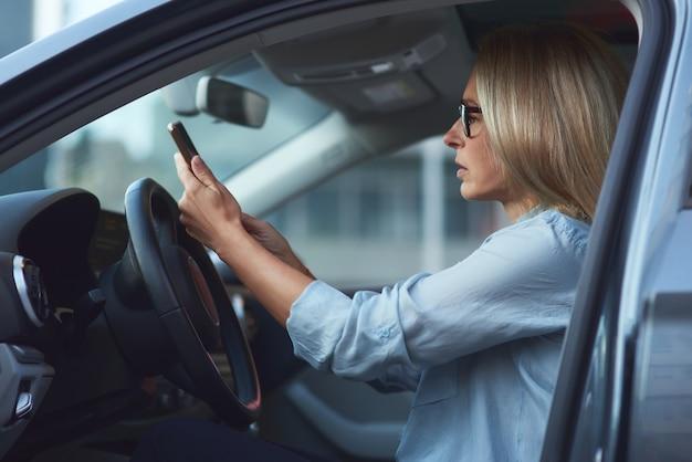 Vista lateral de uma mulher concentrada ou empresária usando óculos, sentada atrás do volante
