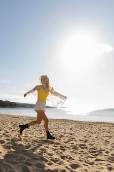 Vista lateral de uma mulher correndo na praia