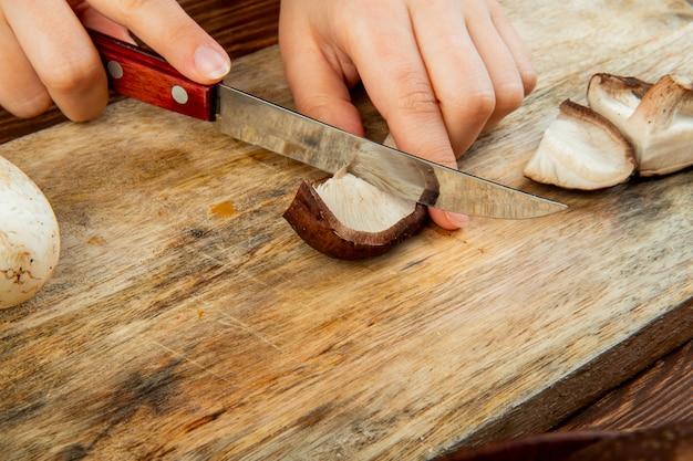 Vista lateral de uma mulher cortando cogumelos frescos com uma faca de cozinha em uma tábua de madeira