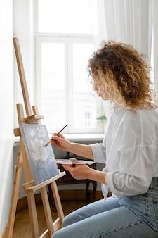 Vista lateral de uma mulher de cabelo encaracolado pintando em casa