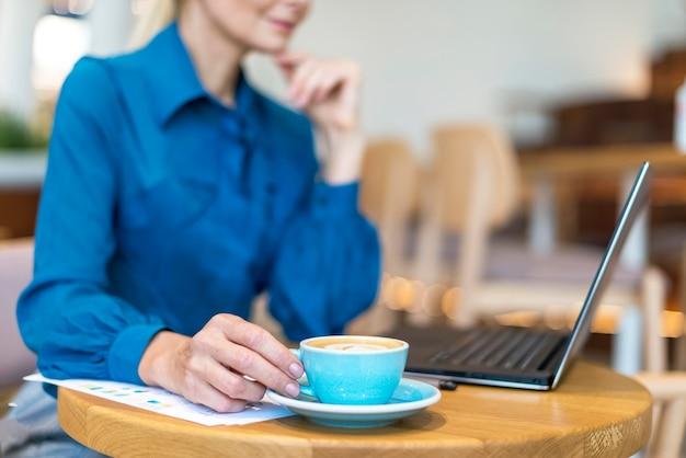 Vista lateral de uma mulher de negócios mais velha desfocada tomando café enquanto trabalhava no laptop