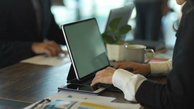 Vista lateral de uma mulher de negócios trabalhando com um tablet e papelada durante uma reunião com um colega de trabalho