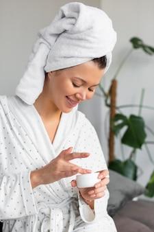 Vista lateral de uma mulher de roupão e toalha usando creme