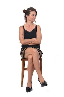 Vista lateral de uma mulher de saia sentada em uma cadeira branca, de lado e braços e pernas cruzados