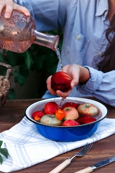 Vista lateral de uma mulher derramando uma água no pêssego segurando sobre a tigela com maçãs frescas