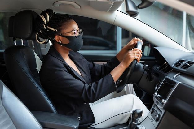 Vista lateral de uma mulher dirigindo seu carro enquanto usava uma máscara facial