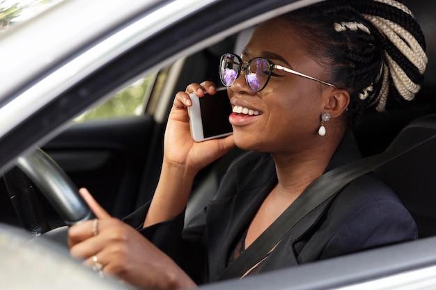 Vista lateral de uma mulher dirigindo um carro particular e falando em um smartphone