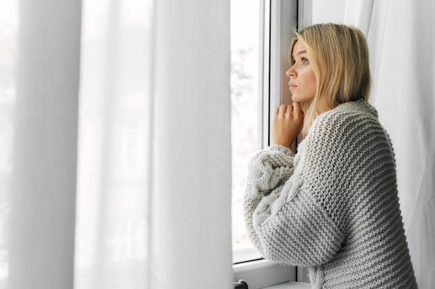 Vista lateral de uma mulher em casa durante a pandemia espiando pela janela