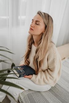 Vista lateral de uma mulher em casa orando com a bíblia