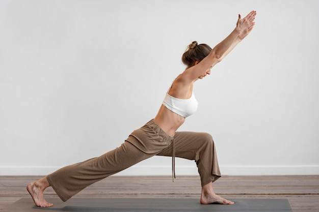Vista lateral de uma mulher em casa praticando ioga com espaço de cópia
