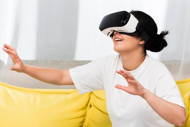Vista lateral de uma mulher em casa usando um fone de ouvido de realidade virtual