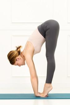 Vista lateral de uma mulher em forma fazendo uma variação uttanasana ou postura de ioga forward bend equilibrando os pés