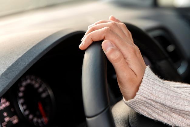 Vista lateral de uma mulher em seu carro segurando o volante enquanto dirige