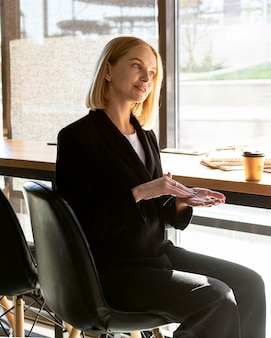 Vista lateral de uma mulher em um café usando linguagem de sinais