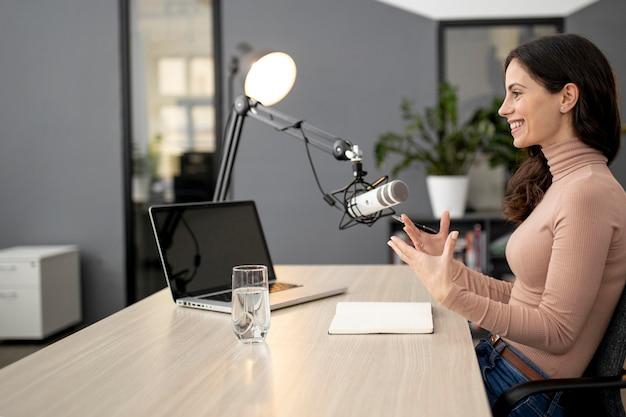 Vista lateral de uma mulher em um estúdio de rádio com microfone e laptop