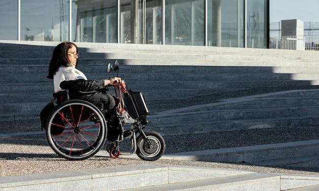 Vista lateral de uma mulher em uma cadeira de rodas na rua com espaço de cópia