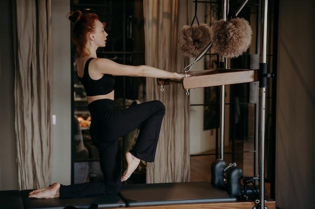 Vista lateral de uma mulher esportiva gengibre em roupas esportivas com corpo atlético, exercitando-se no reformador cadillac, realizando flexibilidade pela perna, alongamento no ginásio. conceito de estilo de vida saudável e fitness