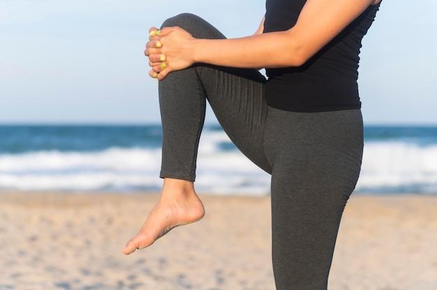 Vista lateral de uma mulher esticando as pernas na praia antes de malhar