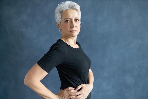 Vista lateral de uma mulher europeia de cabelos grisalhos séria, vestindo uma camiseta preta casual, posando contra o fundo da parede do estúdio de cópia, de mãos dadas na cintura, com expressão facial confiante