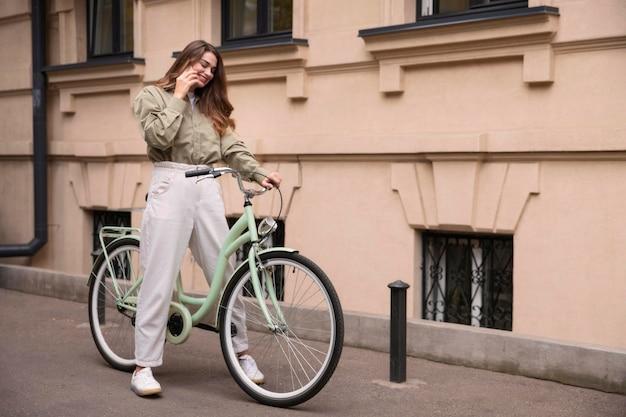 Vista lateral de uma mulher falando ao telefone enquanto andava de bicicleta