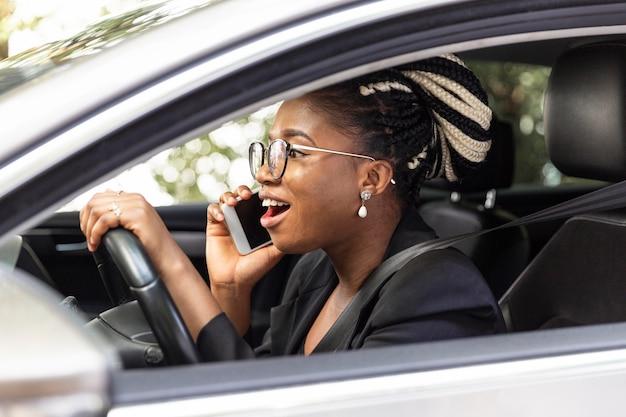 Vista lateral de uma mulher falando no smartphone enquanto dirige o carro