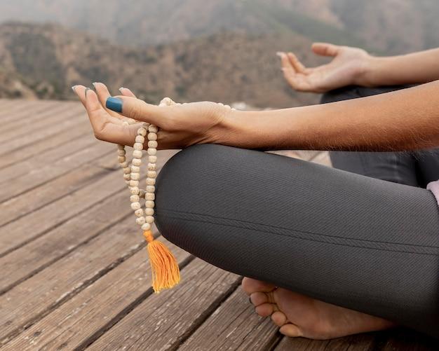 Vista lateral de uma mulher fazendo ioga ao ar livre e segurando um rosário