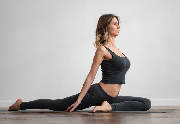 Vista lateral de uma mulher fazendo ioga em casa no tapete