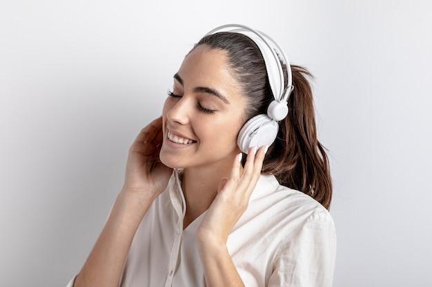 Vista lateral de uma mulher feliz com fones de ouvido