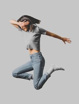 Vista lateral de uma mulher feliz pulando no ar
