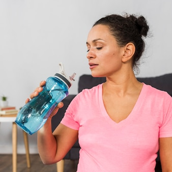 Vista lateral de uma mulher grávida bebendo água enquanto se exercita em casa