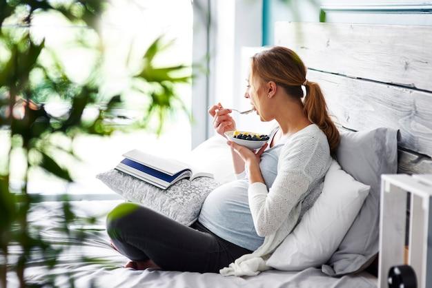 Vista lateral de uma mulher grávida relaxando em seu quarto