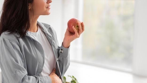 Vista lateral de uma mulher grávida segurando uma maçã com espaço de cópia