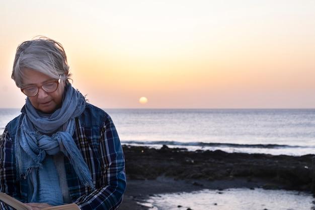 Vista lateral de uma mulher idosa, aproveitando seu tempo livre lendo um livro sentado perto da praia. um povo relaxado. horizonte sobre o mar e o pôr do sol