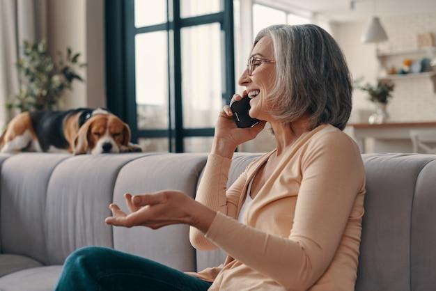 Vista lateral de uma mulher idosa bonita em roupas casuais, falando ao telefone inteligente e sorrindo enquanto está sentada no sofá em casa