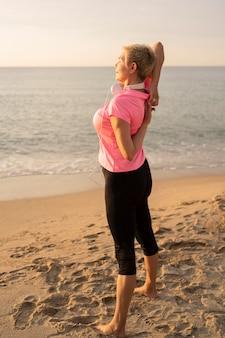 Vista lateral de uma mulher idosa com fones de ouvido estendendo-se na praia