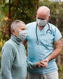 Vista lateral de uma mulher idosa com máscara médica e enfermeiro