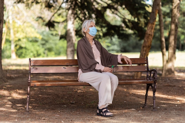 Vista lateral de uma mulher idosa com máscara médica sentada no banco ao ar livre em uma casa de repouso