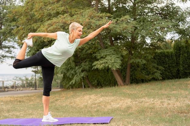 Vista lateral de uma mulher idosa praticando ioga ao ar livre no parque