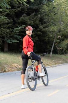 Vista lateral de uma mulher idosa sorridente ao ar livre andando de bicicleta