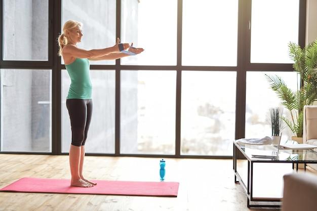 Vista lateral de uma mulher loira atlética em roupas esportivas, se exercitando com banda de resistência, seguindo online