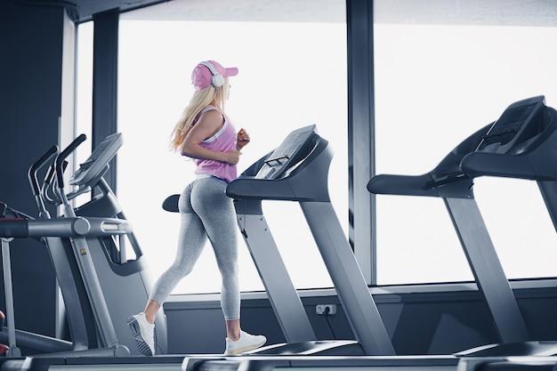 Vista lateral de uma mulher loira desportiva com boné rosa fazendo exercícios na esteira na academia