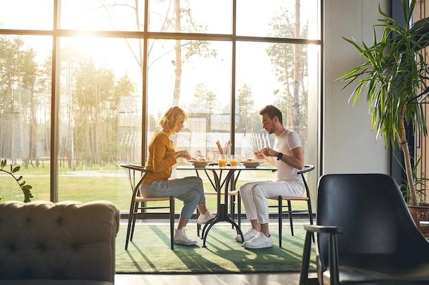 Vista lateral de uma mulher loira focada e seu jovem marido sério almoçando juntos