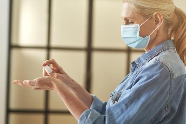 Vista lateral de uma mulher loira madura com máscara protetora, limpando as mãos com antibacteriano
