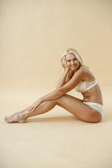 Vista lateral de uma mulher loira madura feliz com corpo em forma, posando de cueca, apoiando-se nos joelhos enquanto
