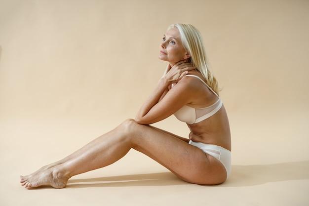 Vista lateral de uma mulher loira sensual posando de cueca sentada no chão do estúdio e olhando para longe