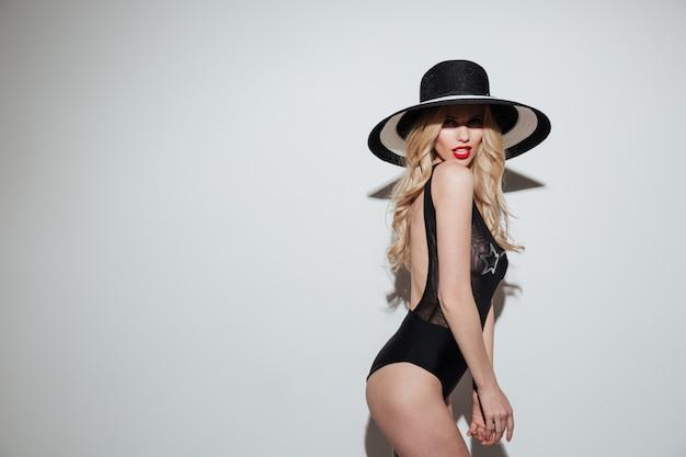 Vista lateral de uma mulher loira sexy sensual no chapéu