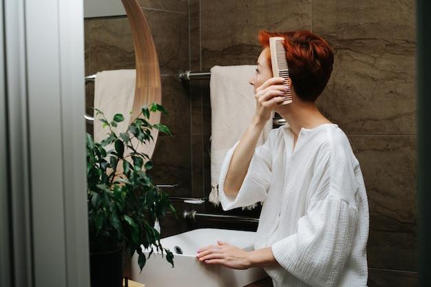Vista lateral de uma mulher madura de cabelos curtos, penteando o cabelo com um pente de madeira. ela está parada na frente do espelho em um banheiro.