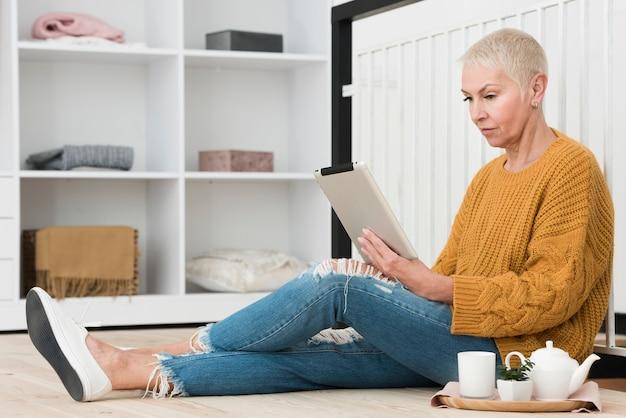 Vista lateral de uma mulher madura, olhando para tablet