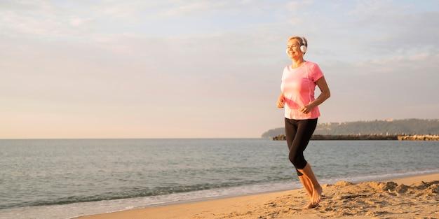 Vista lateral de uma mulher mais velha com fones de ouvido correndo na praia