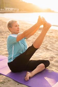 Vista lateral de uma mulher mais velha fazendo ioga na praia